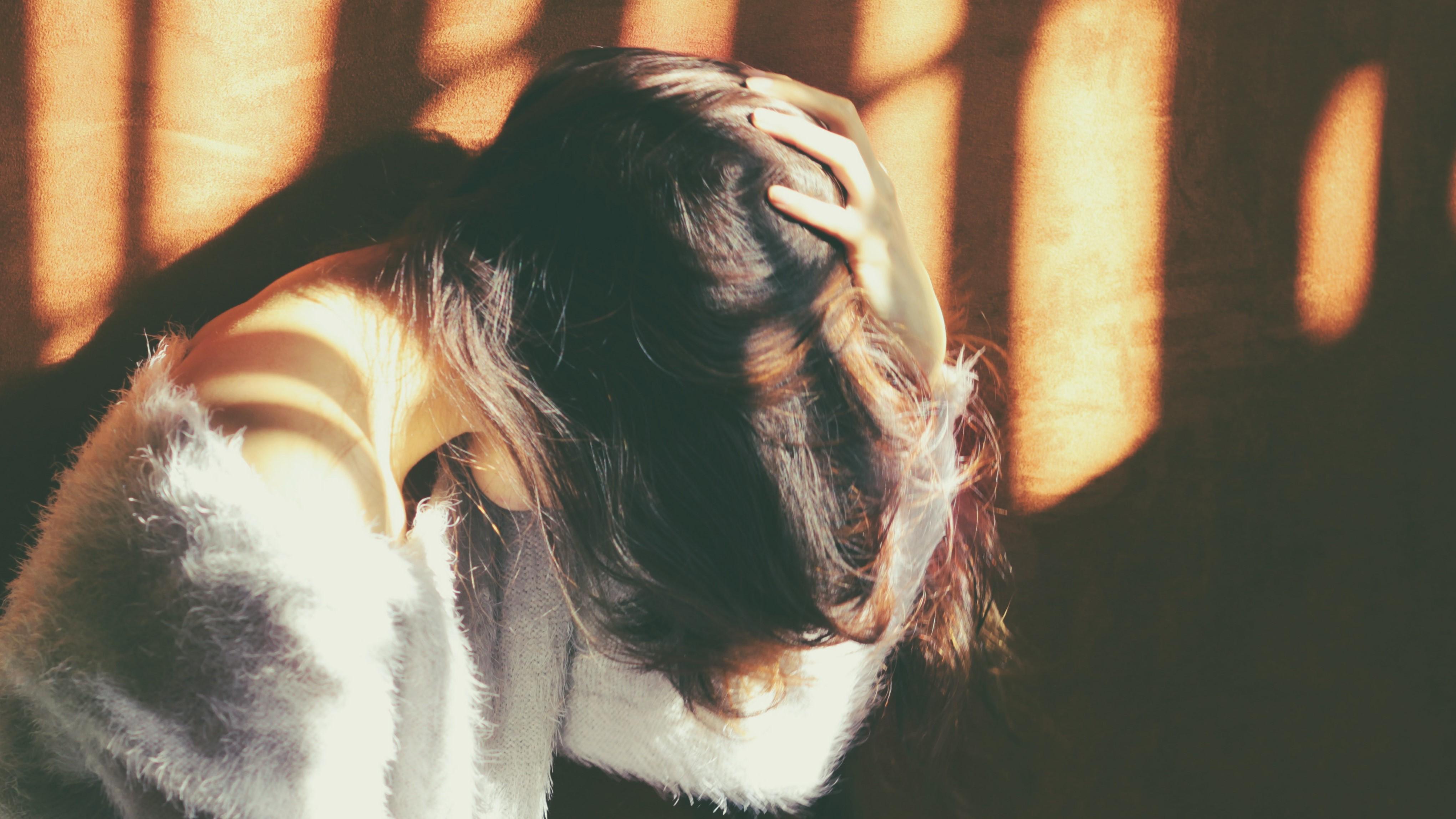 Trauriges Mädchen vor einer Wand im Schatten