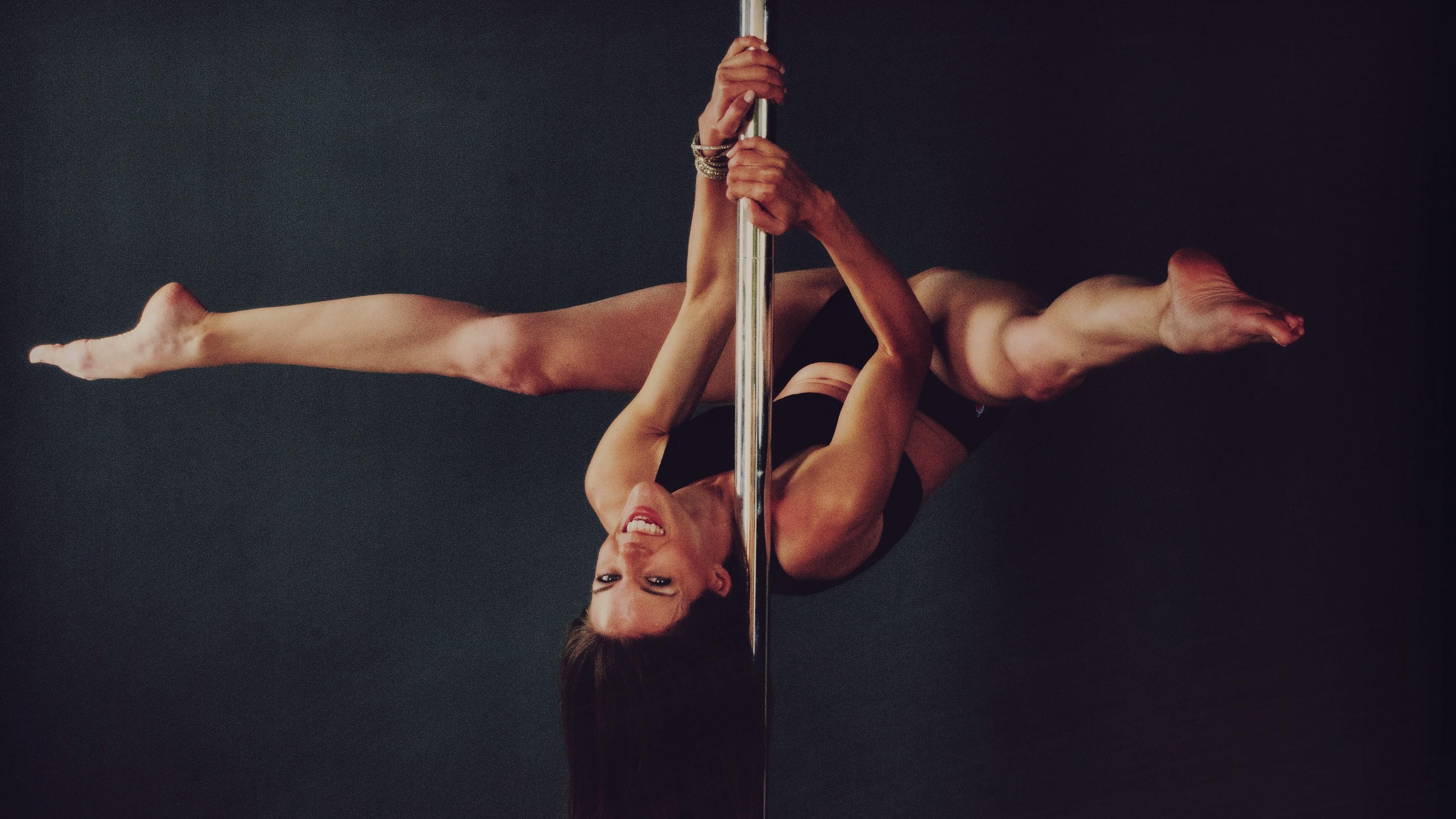 Sportliche Frau tanz an einer Poledancestange